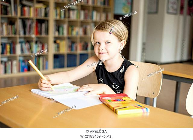 Portrait of cute girl drawing with color pencil in classroom