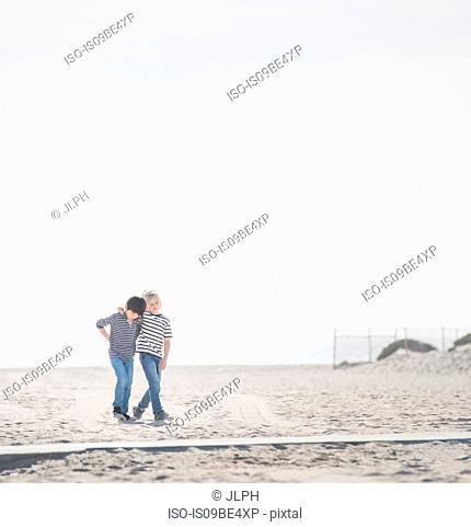 Boys walking on sandy beach