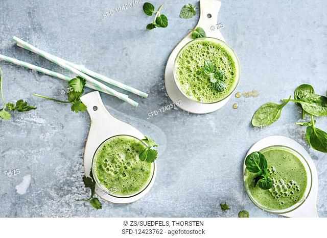 Three green smoothies with bok choy, melon, spinach, lamb's lettuce and kiwi