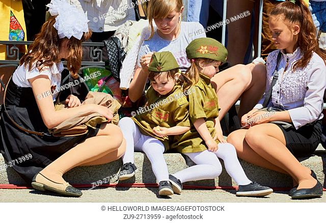 Two small girl spectators in uniform at 9th May Victory Day parade, Sebastopol, Crimea. . Commemorates the end of Russian involvement in World War 2