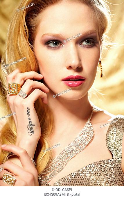 Close up portrait of young woman with hand tattoo