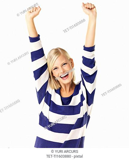 Studio portrait of young woman cheering