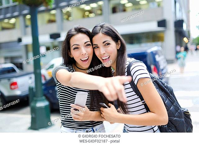 USA, New York City, two happy twin sisters with cell phones in Manhattan
