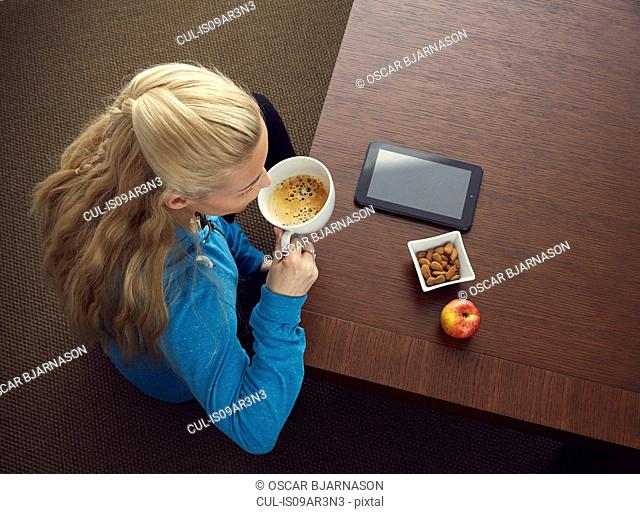 Woman drinking coffee, digital tablet, almonds, apple on table