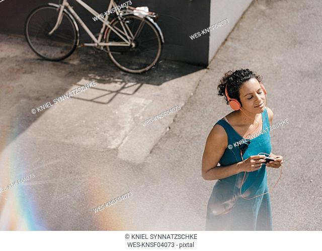 Woman standing in backyard, wearing headphones, listening music
