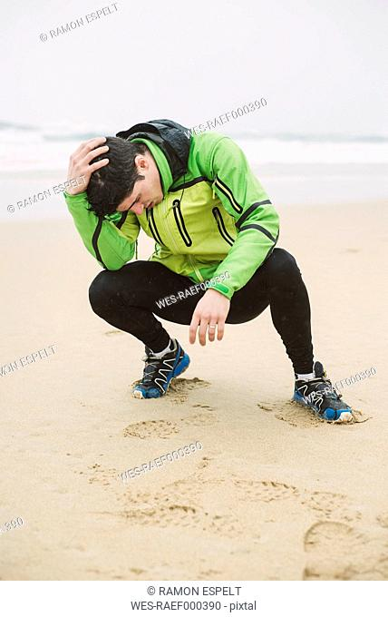 Spain, Valdovino, exhausted young man after jogging on the beach at rainy day