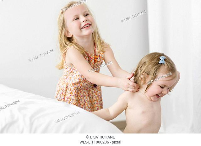 Two little sisters playing tag in the bedroom