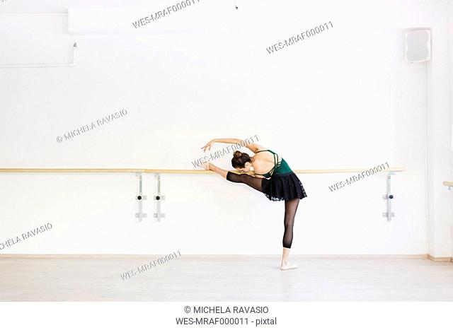 Dancer practicing at the barre in the gym