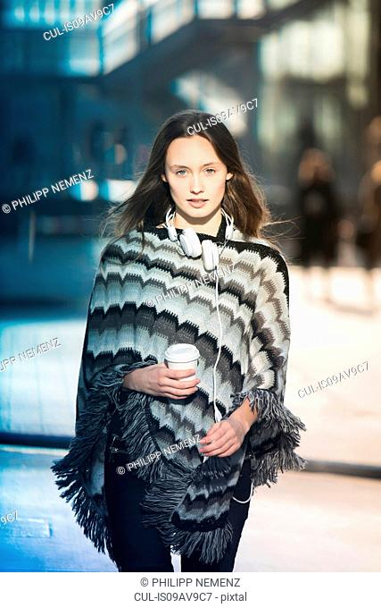 Portrait of mid adult woman wearing poncho strolling on city street