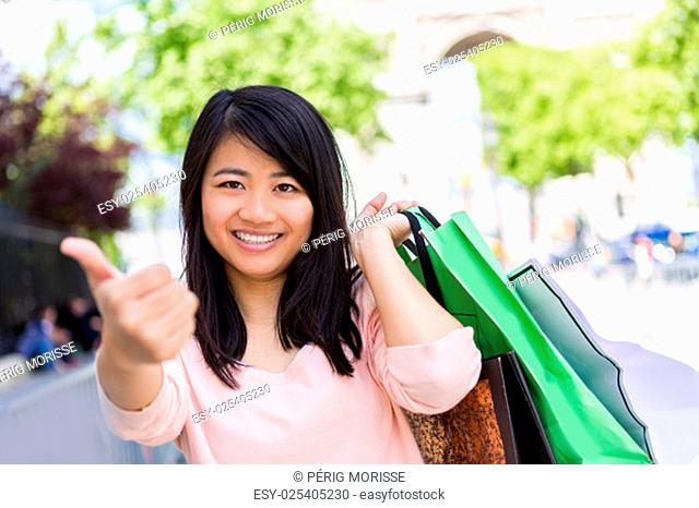 View of a Young attractive asian tourist doing shopping in Paris