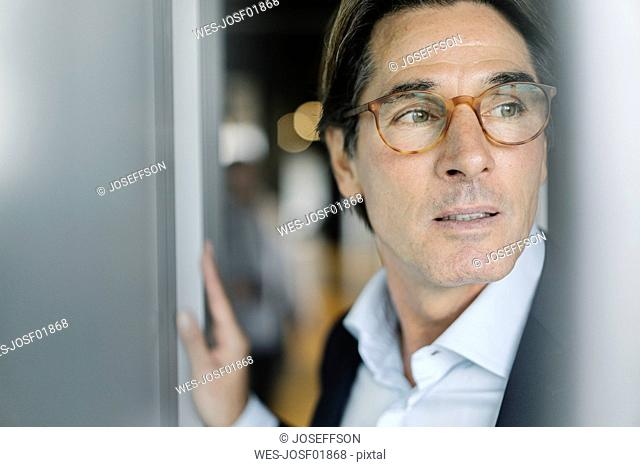 Portrait of businessman wearing glasses in office