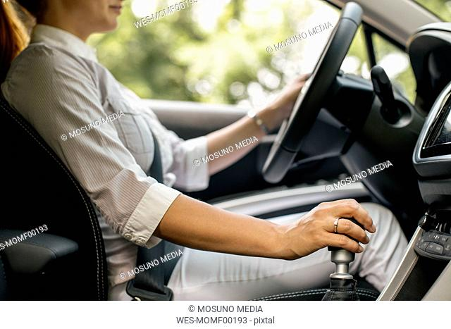Businesswoman driving car, partial view