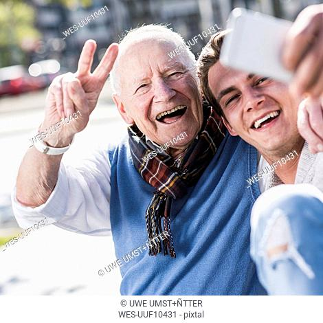 Happy senior man and adult grandson taking a selfie