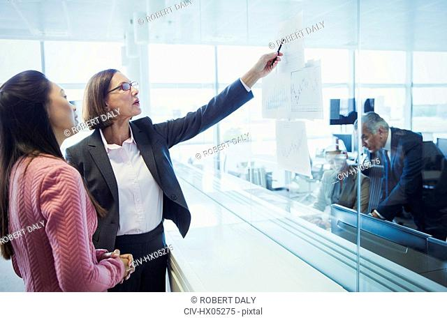 Businesswomen discussing chart in office