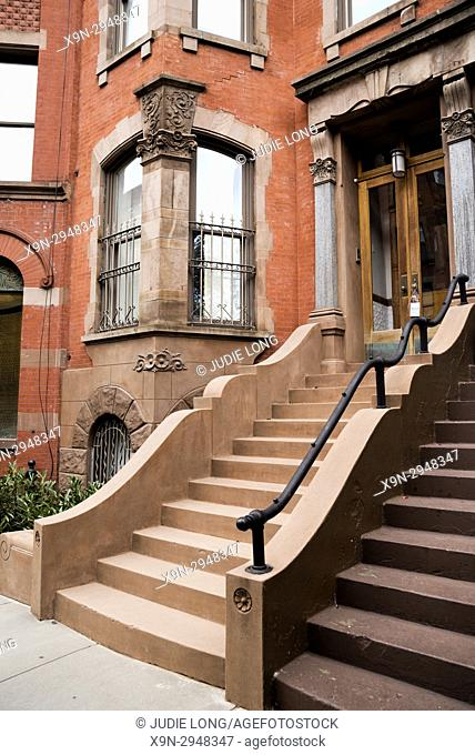 New York City, Manhattan, Upper West Side. Close up of Two Attached Brownstone Townhouses, Curved Entry Stairway on one, Distinctive Corner Windows on the Other