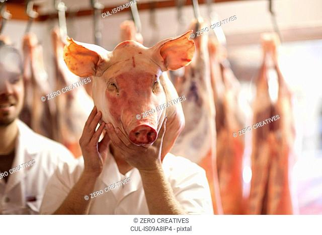 Butcher holding pig's head in front of face