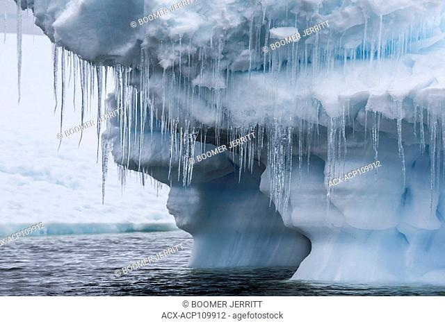 Large icicles hang from an undercut iceberg grounded in water near Pleneau Island, Antarctic Peninsula
