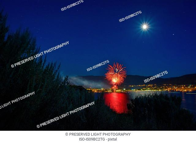 Canada Day celebration over Okanagan Lake, full moon in sky, Penticton, British Columbia, Canada