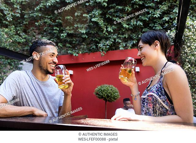 Happy couple having a beer outside