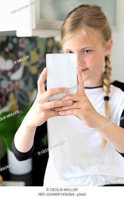 Girl taking picture of herself with smartphone