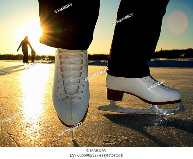 Ice skating. Ice skates in action closeup outdoors. Classic figure ice skates on frozen lake outdoors in evening light, Mom and daughter silhouette in the...