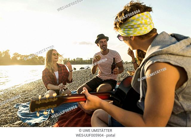Friends with guitar relaxing at the riverside at sunset