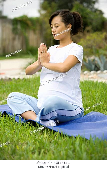 Pregnant woman in yoga position on lawn