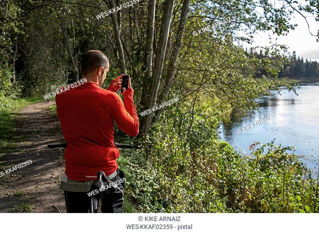 Mountain biker standing at lake taking pictures with his smartphone
