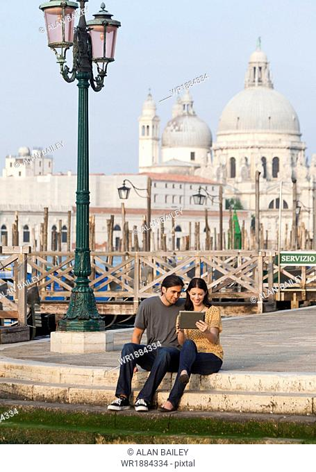 Italy, Venice, Young couple using digital tablet, Santa Maria Della Salute church in background
