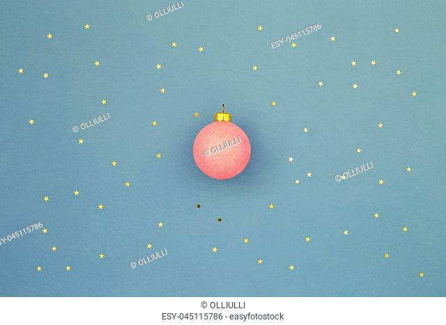 Pink Christmas ball on blue holiday background with gold stars sequins. Minimal New Year greeting card. Shining Night sky at christmas concept