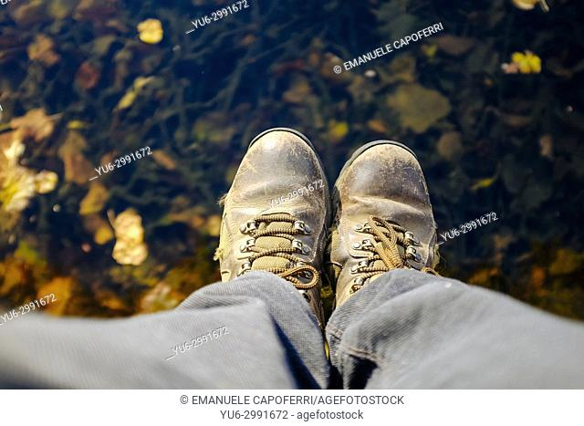 feet with rocking boots over water