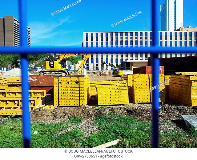 Looking through a blue wire fence at yellow palettes and a crane during the construction of the new Windsor City Hall