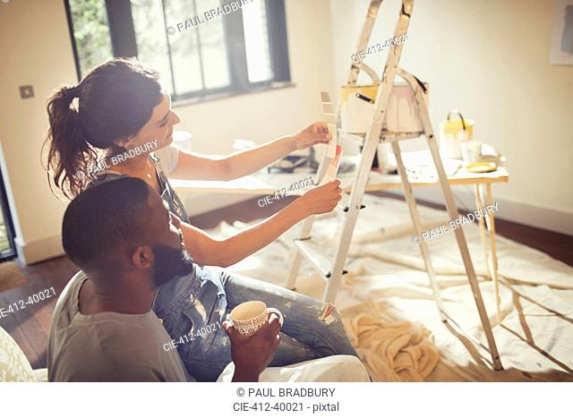 Couple viewing paint swatches, painting living room
