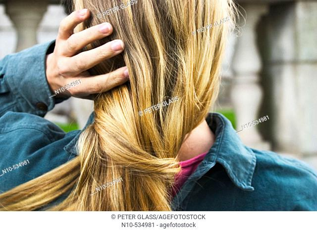 Young blond woman fixing her hair