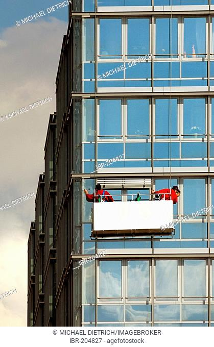 Window cleaners work on a multistoried building in Kiel, Schleswig-Holstein, Germany