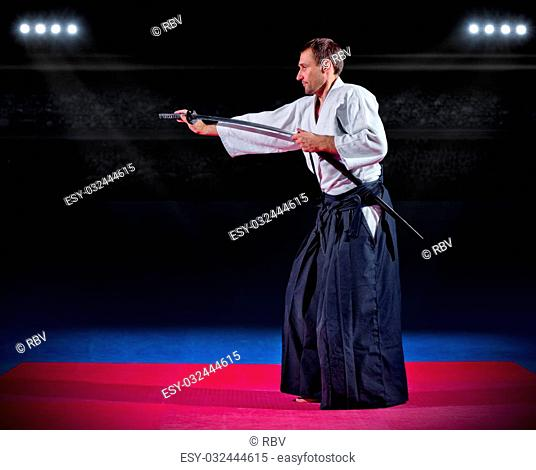 Martial arts fighter with sword at sports hall