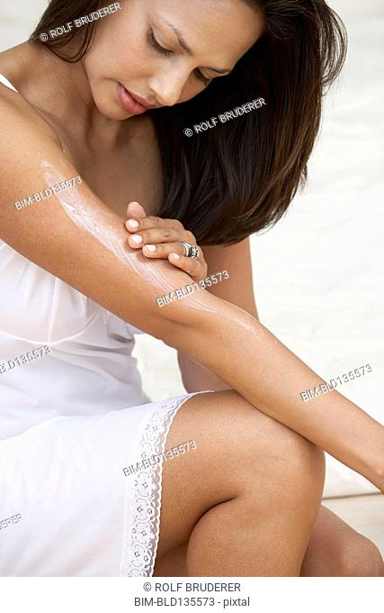 Indian woman applying moisturizer