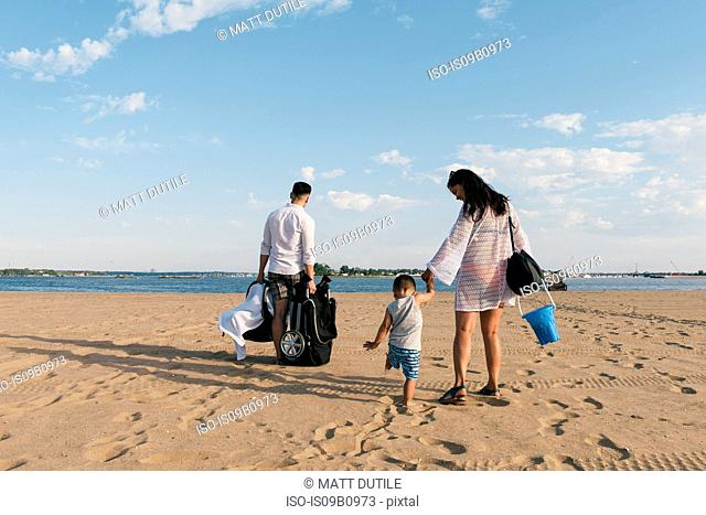 Rear view of parents strolling with toddler son on beach at Pelham Bay Park, Bronx, New York, USA