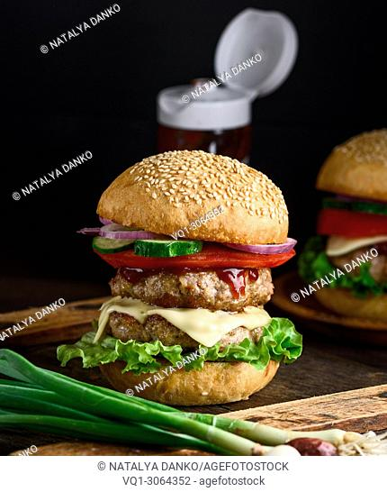 double cheeseburger in a bun with sesame seeds, in the middle fresh vegetables and meat cutlets
