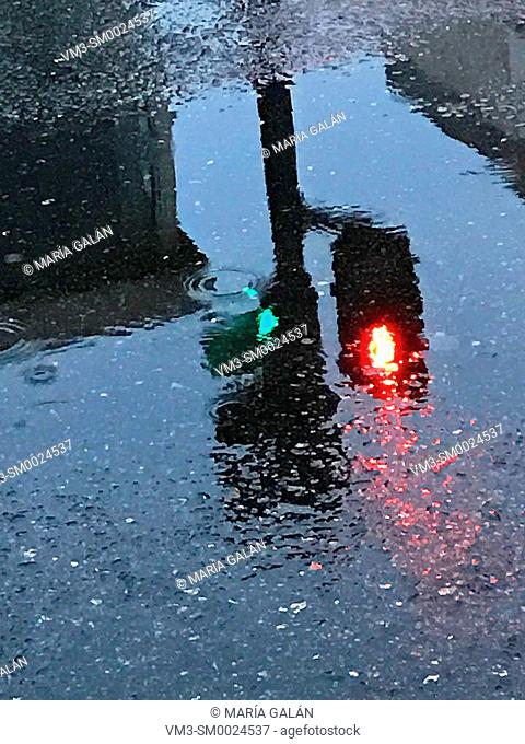 Traffic light reflected on the water of a puddle in a rainy day