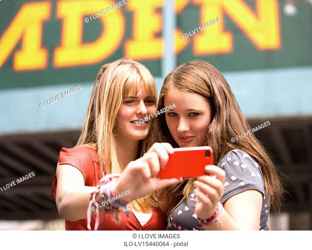 Two teenage girls taking a photograph of themselves in Camden, London UK