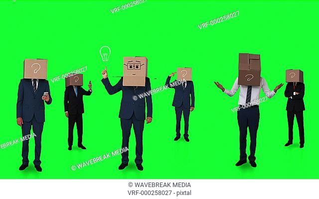 Team of businessman hiding head with box