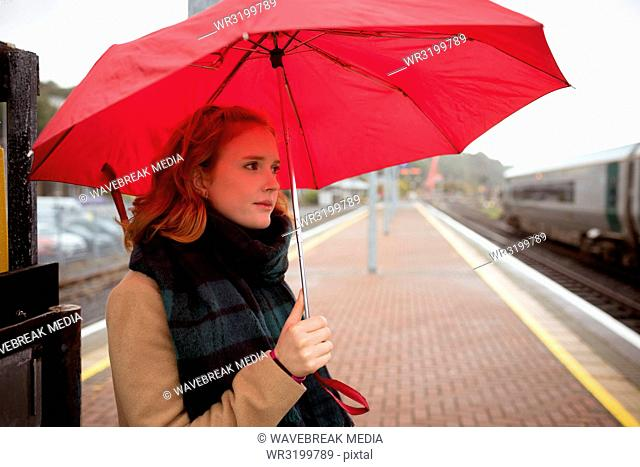 Young woman with umbrella waiting for train on platform