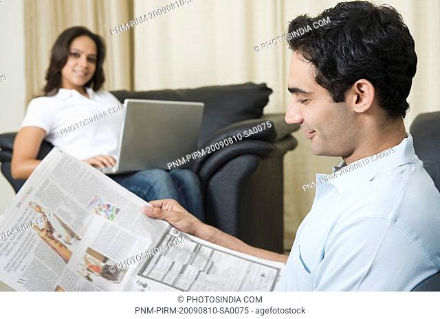 Man reading a newspaper with his wife using a laptop