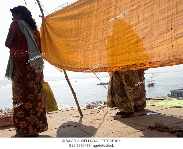 Traditionaly dressed women drying clothes at the ghats in Varanasi, Uttar Pradesh, India