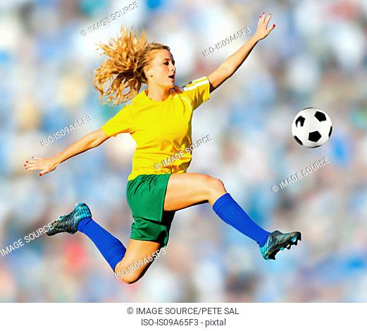Soccer player kicking in mid-air