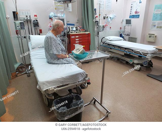 A senior man sitting on an examination bed in emergency at a hospital waiting for a doctor