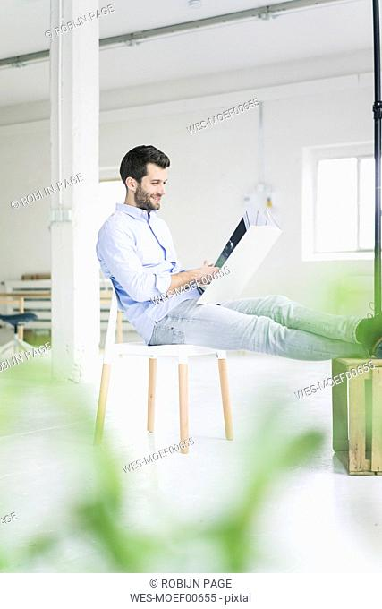 Businessman sitting in empty loft office holdig large folder
