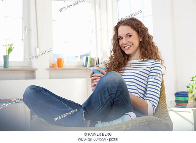 Smiling woman at home sitting in chair