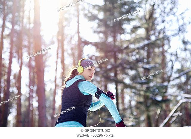 Young woman with headphones jogging in forest